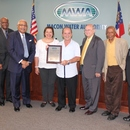 Alfredo Daniel (center) receives a resolution from the MWA Board commemorating his retirement from the water utility.